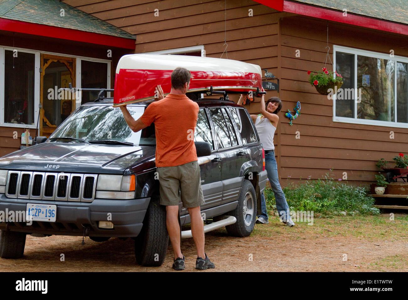 Young couple load canoe on roof of vehicle at cottage near Oxtongue Lake, Muskoka, Ontario, Canada. - Stock Image