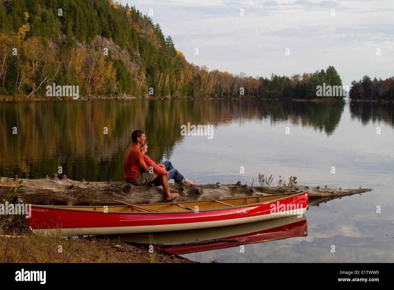 Young couple enjoy quite evening beside canoe on Oxtongue Lake, Muskoka, Ontario, Canada. - Stock Image