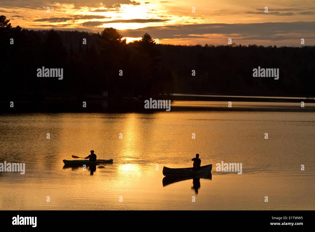 Two men paddle canoe and kayak on Oxtongue Lake at sunrise, Muskoka, Ontario, Canada. - Stock Image