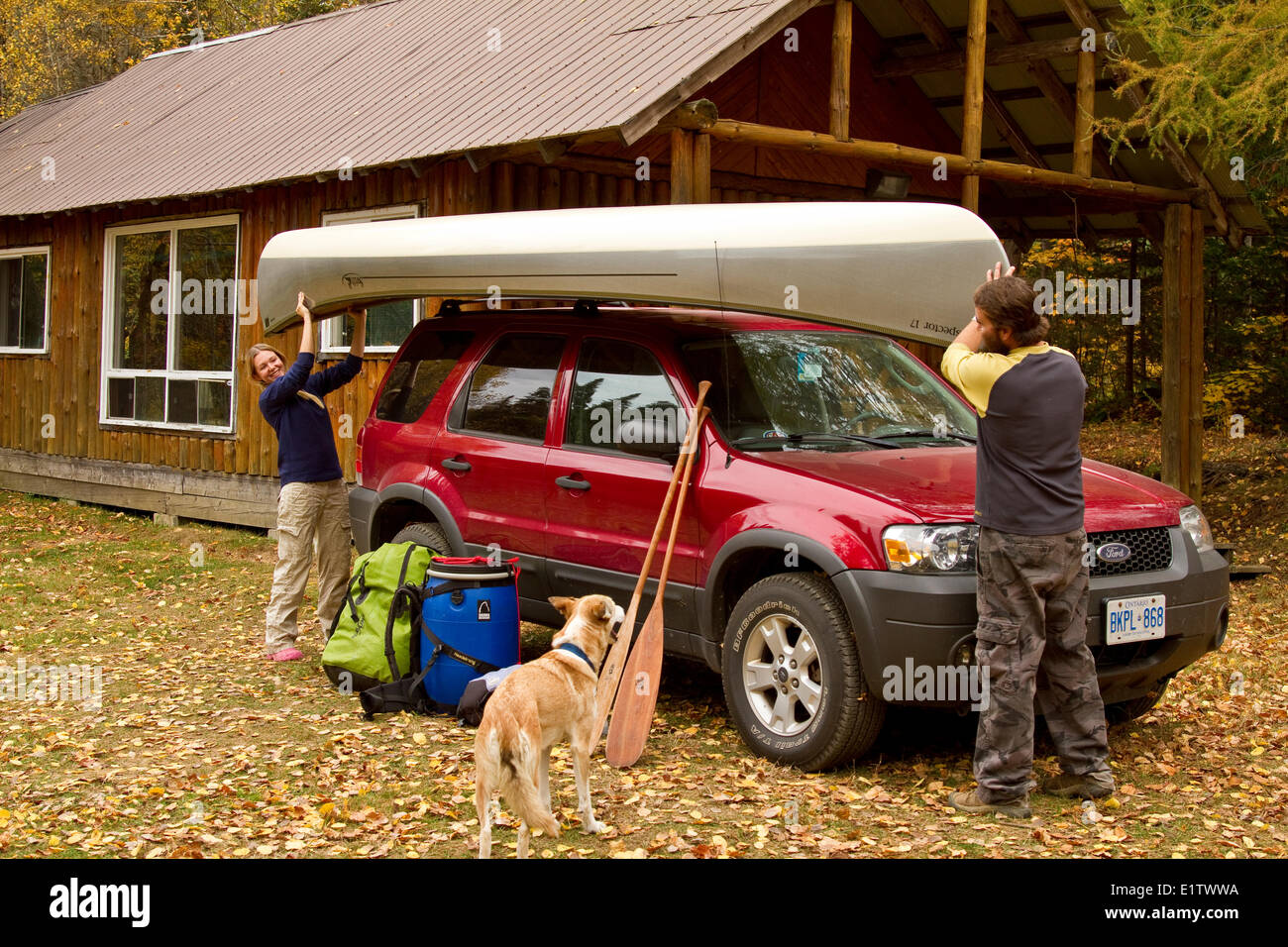 Young couple load canoe on roof of vehicle at cottage near South River, Algonquin Park, Ontario, Canada. - Stock Image