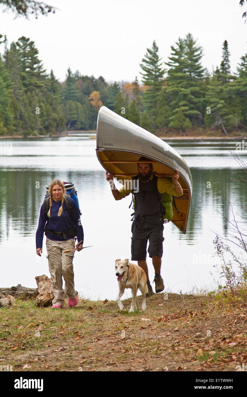 Young couple portage canoe from small lake in northwestern end of Algonquin Park, Ontario, Canada. Stock Photo