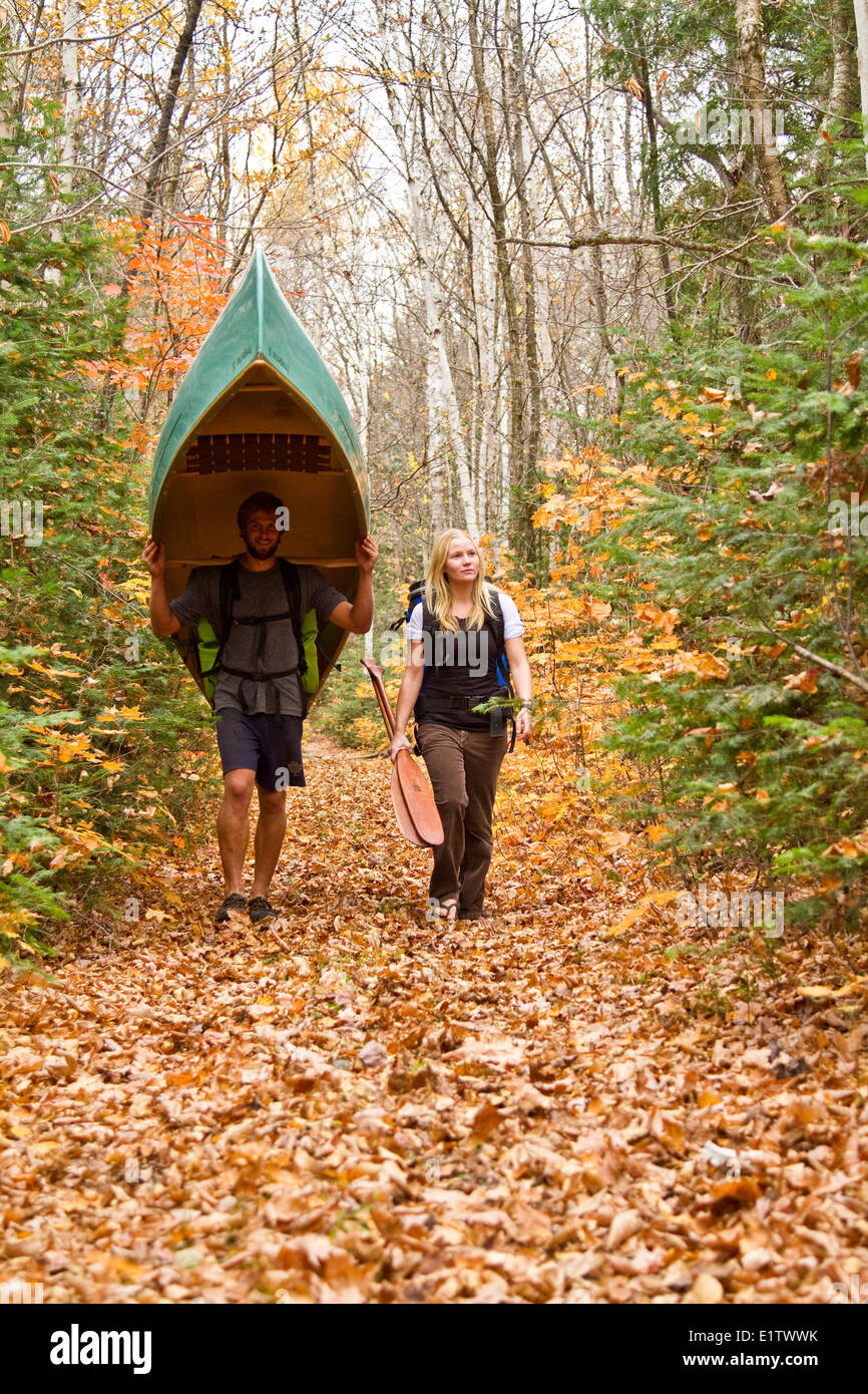 Young couple portage canoe  in northwestern end of Algonquin Park, Ontario, Canada. - Stock Image