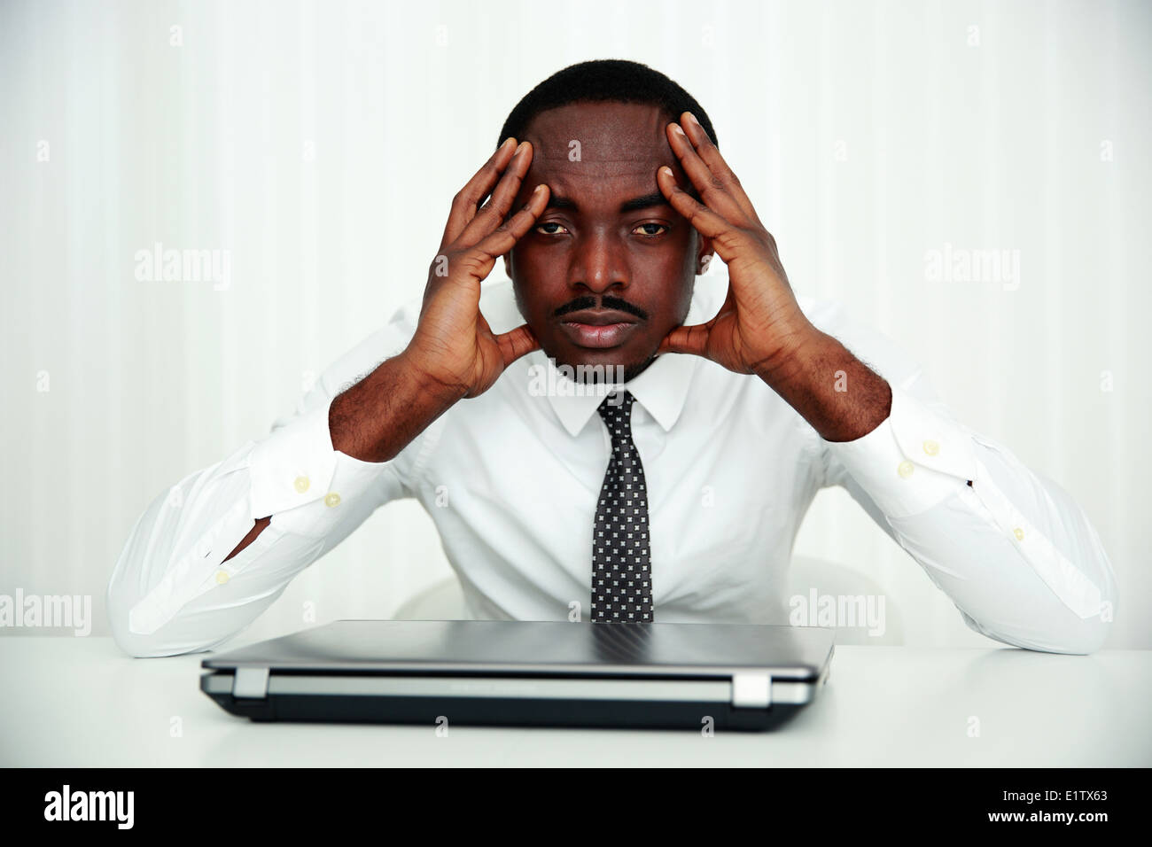 Pensive african businessman sitting at his workplace in office - Stock Image