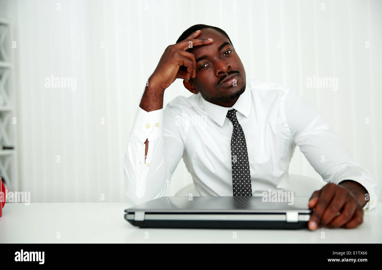 African businessman sitting at his workplace in office - Stock Image