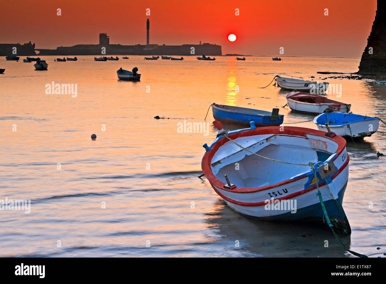Small fishing boats anchored at Playa de la Caleta at sunset in the City of Cadiz, Province of Cadiz, Costa de la - Stock Image