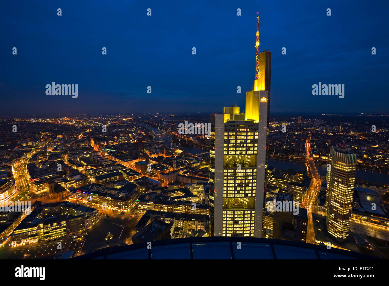Commerzbank Tower illuminated with yellow lights at dusk as seen the Main Tower in the City Frankfurt am Main Hessen Stock Photo