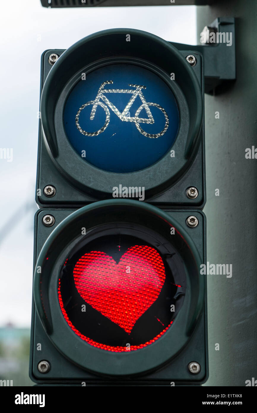 Red heart painted on stop light for bicycles in Berlin Germany - Stock Image