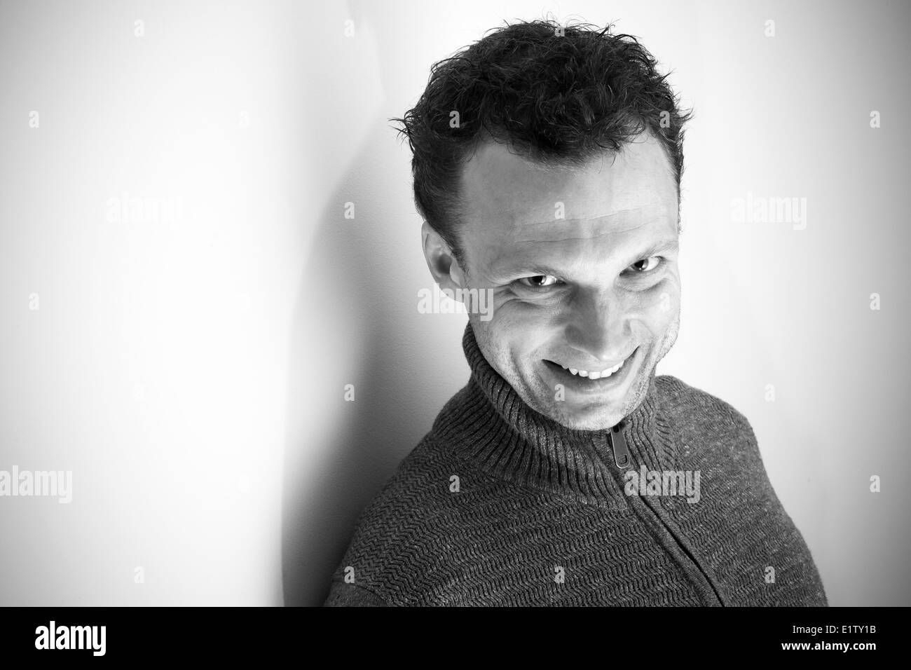 Angry laughing young Caucasian man monochrome portrait - Stock Image