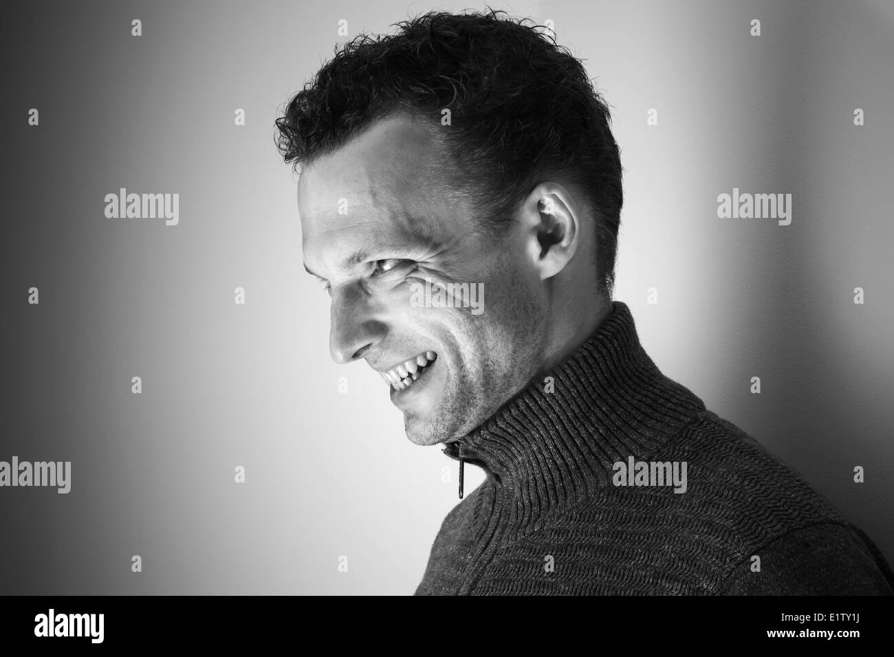 Angry laughing young Caucasian man black and white portrait - Stock Image