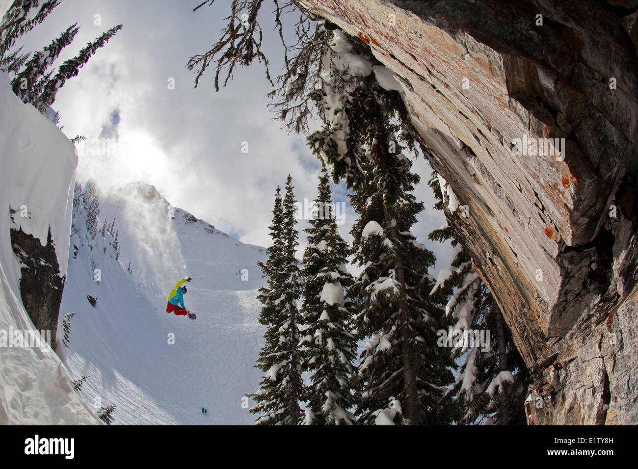 A male snowboarder airs off a big cliff at Revelstoke Mtn Resort, BC - Stock Image