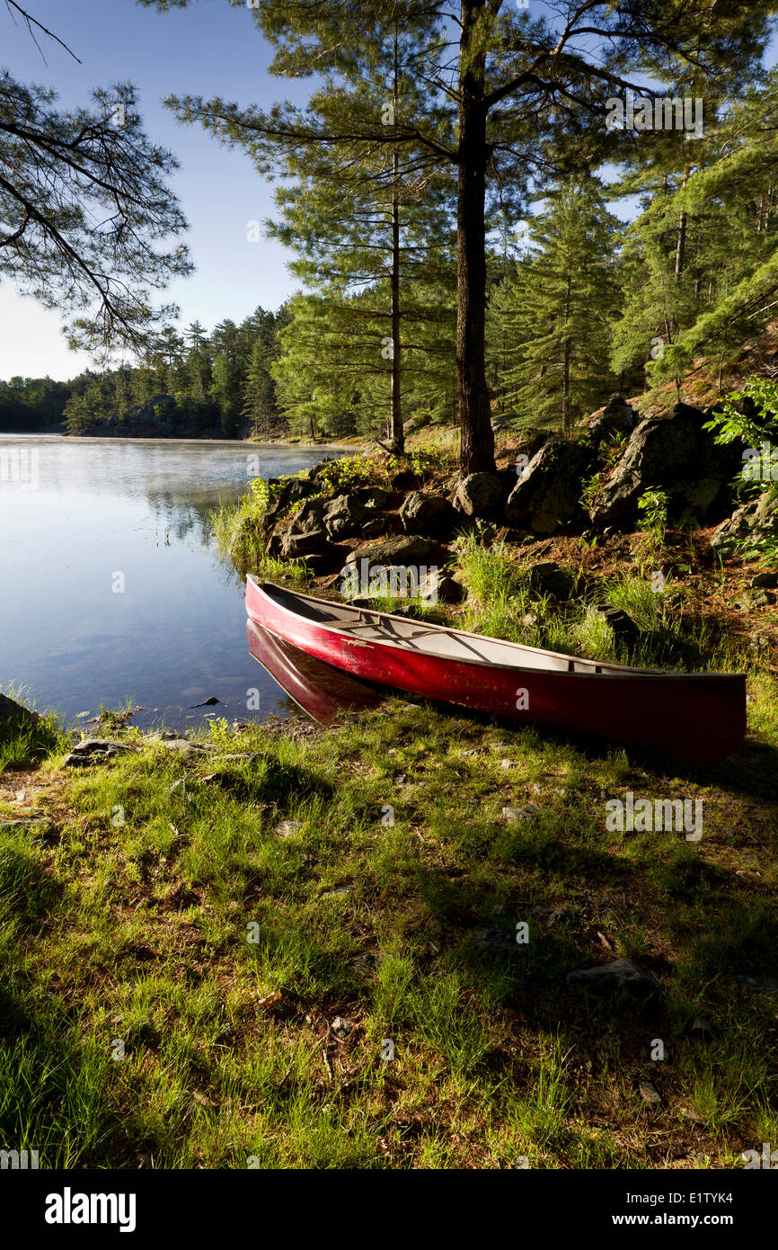 Red Canoe at the portage on Freeland Lake in Killarney Provincial Park, Ontario - Stock Image