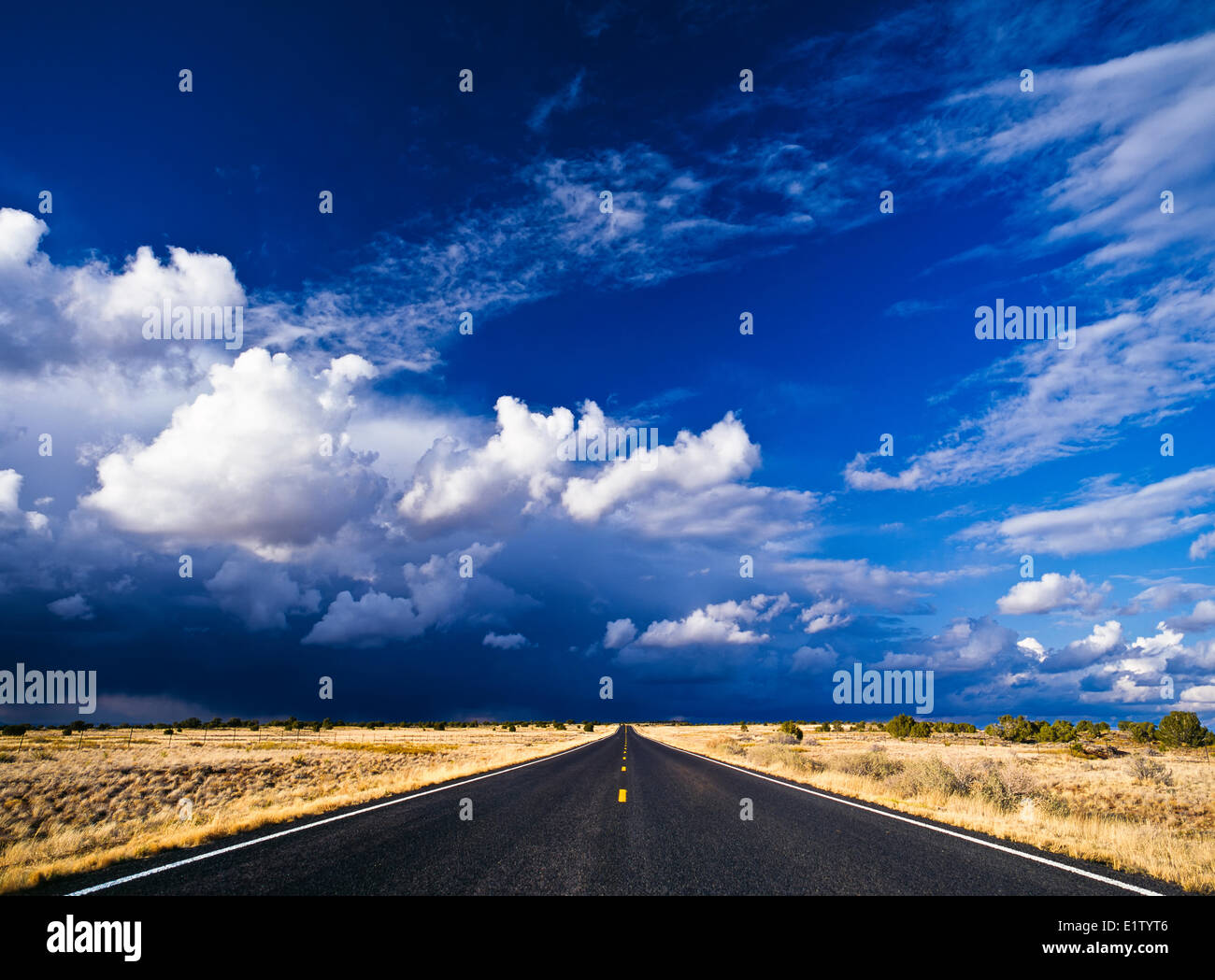 Thunderstorm and storm clouds above a desert road highway in New Mexico, USA. - Stock Image