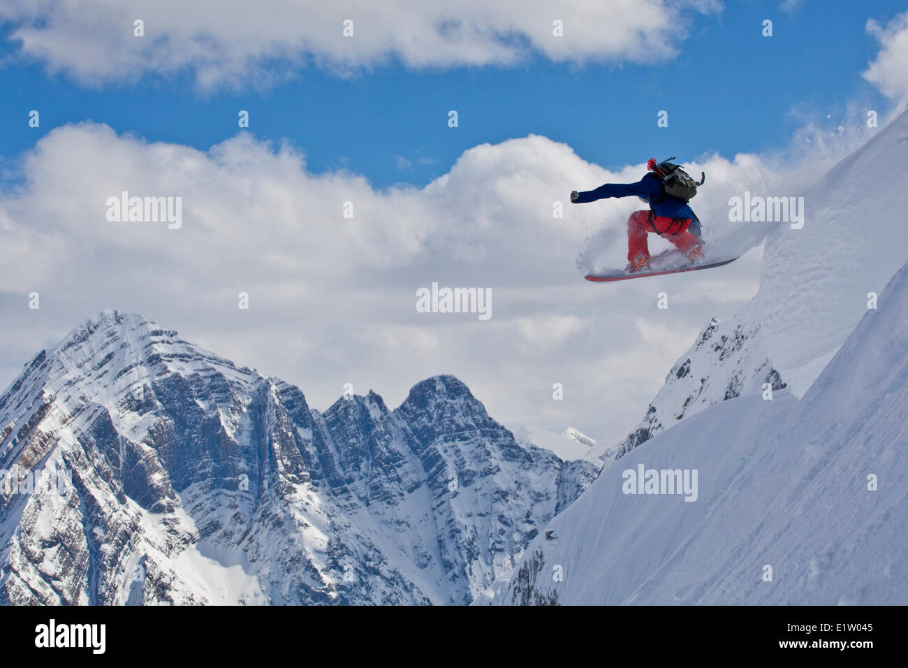 A male backcountry snowboarder airs a pillow with classic canadian rockies scenery as a backdrop. Icefall Lodge, - Stock Image