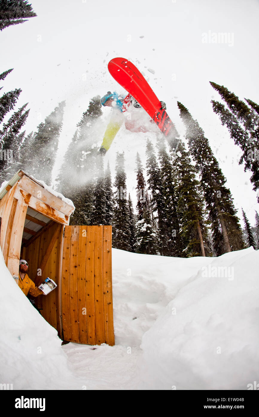 A male backcountry snowboarder airs an outhouse, Icefall Lodge, Canadian Rockies, Golden, BC - Stock Image