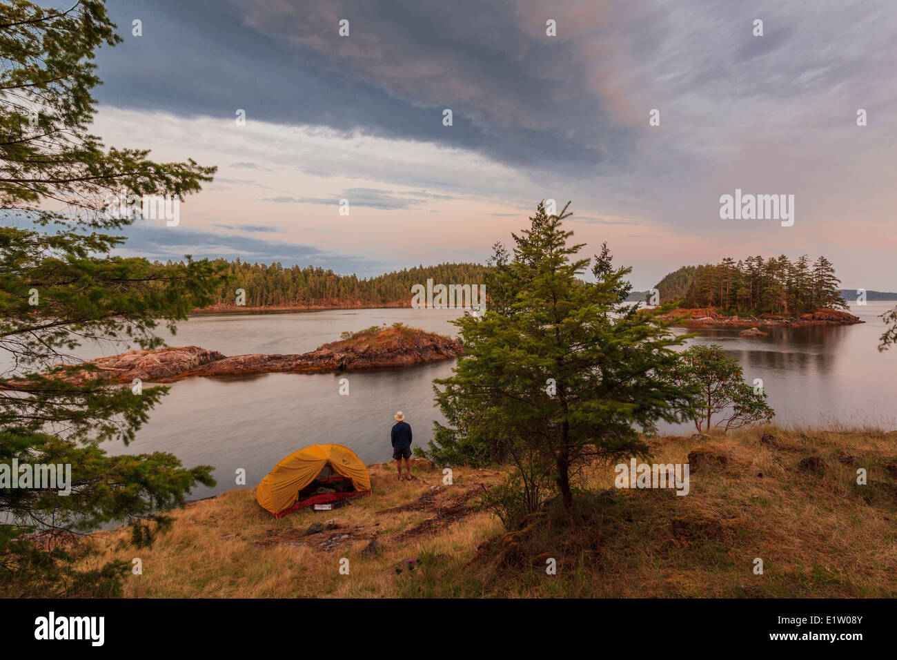 A camper enjoys the sunset on Penn Island in Sutil Channel between Read and Cortes Islands British Columbia Canada.Model - Stock Image