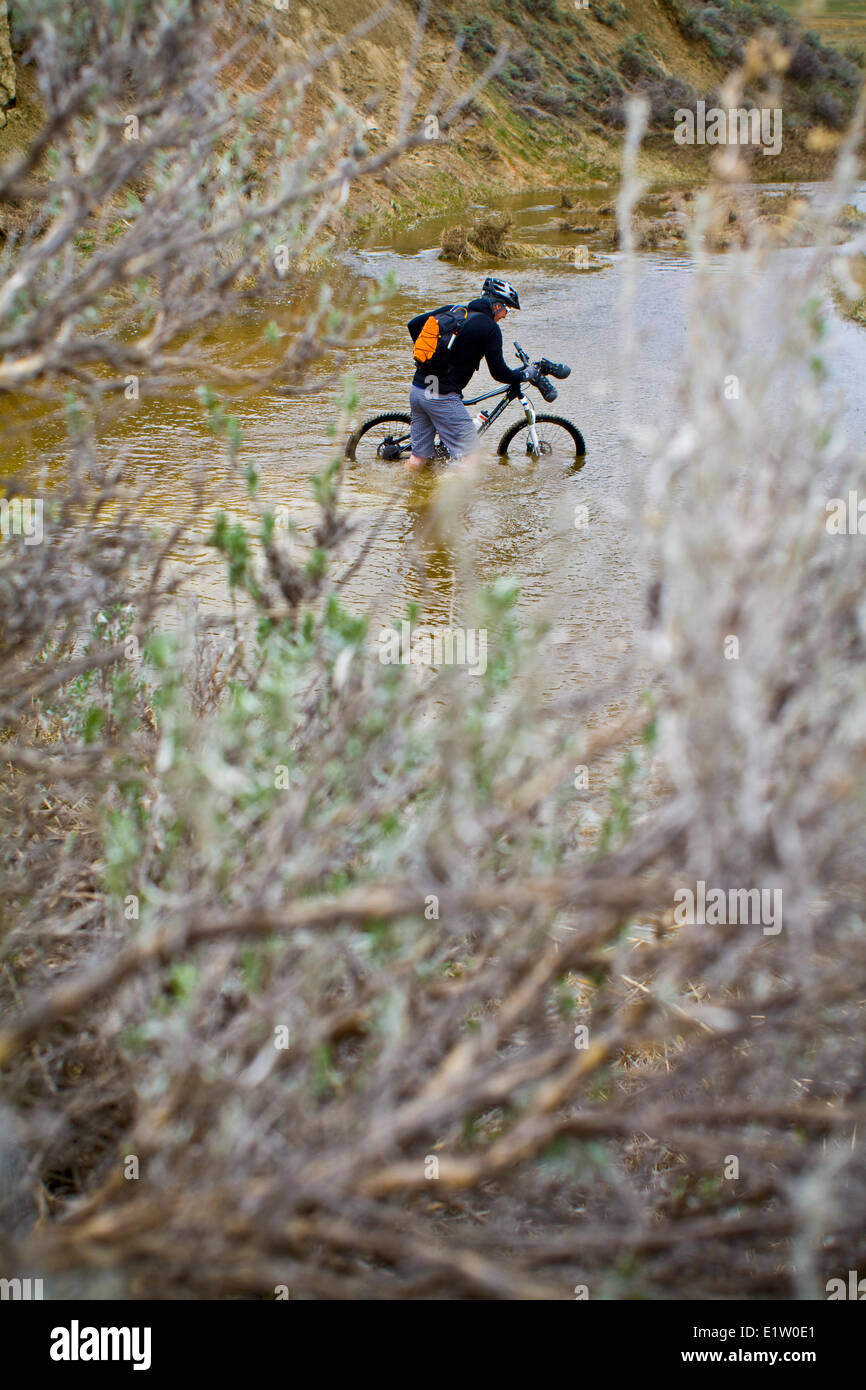 A man pushes his mountain bike through spring run off conditions on the Maah Daah Hey Trail, North Dakota Stock Photo