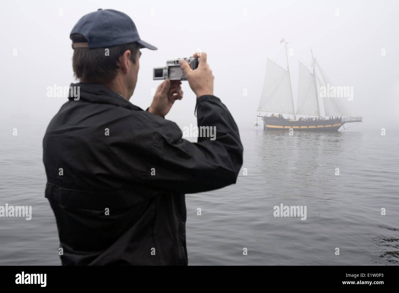 A man photographs sailing ship Liana's Ransom as it navigates thick fog in Halifax Harbour during the 2009 Tall - Stock Image