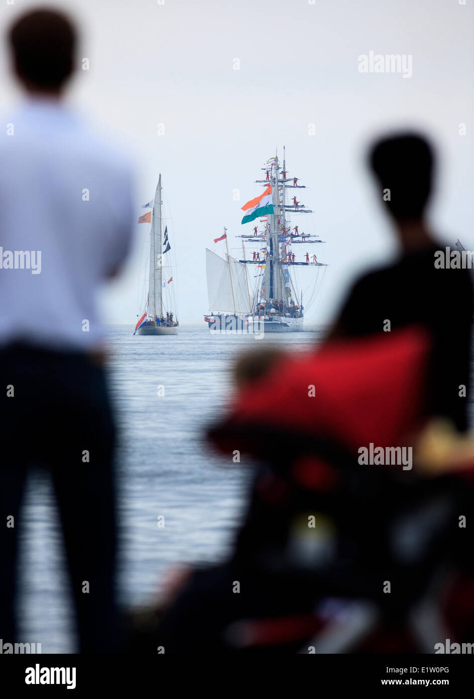 Sailing ships head to sea as people watch the Parade of Sail conclusion of the 2007 Tall Ships festival in Halifax, - Stock Image