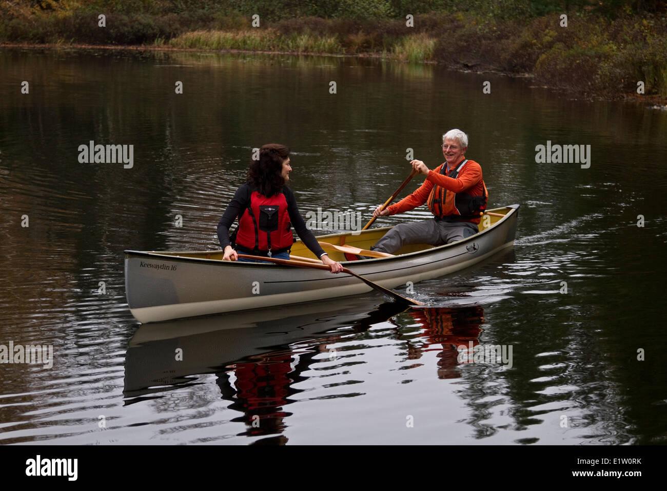Middle-aged couple paddling canoe in serene setting on Oxtongue Lake, Muskoka, Ontario, Canada. - Stock Image