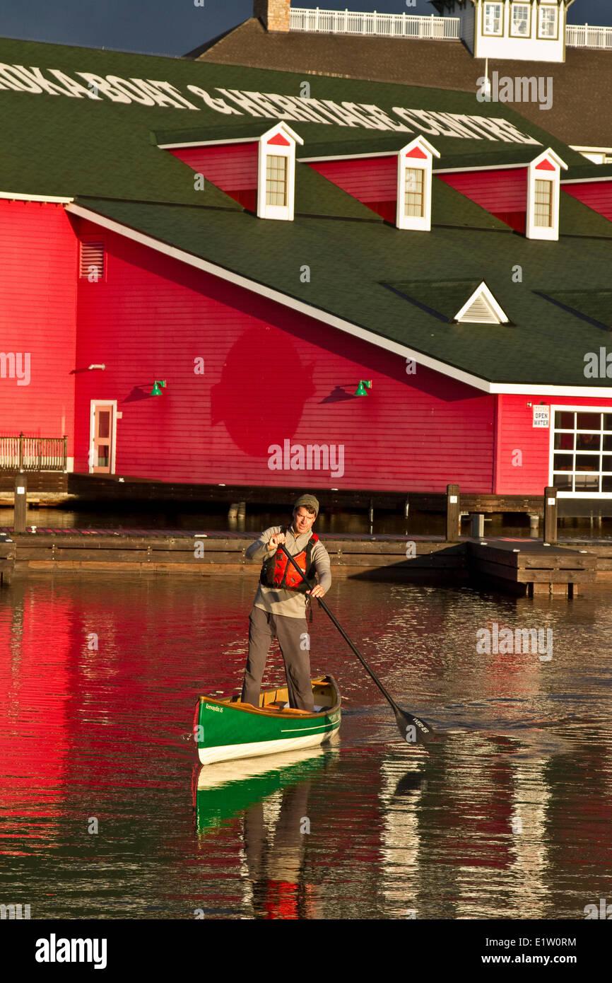 Young man practises stand-up paddling in canoe on Lake Muskoka, Bracebridge, Ontario, Canada. - Stock Image