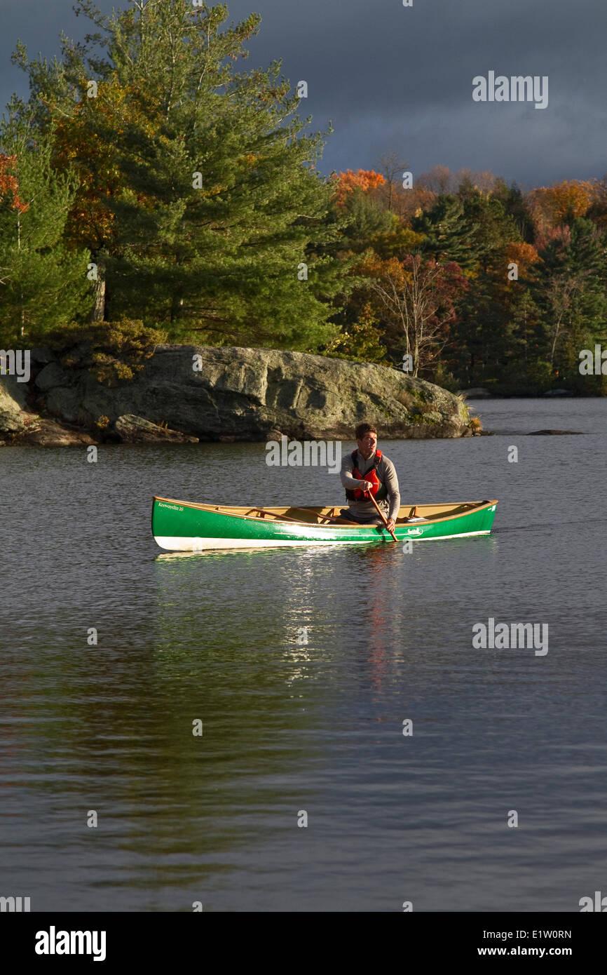 Young man paddling canoe on Lake Muskoka, Bracebridge, Muskoka, Ontario, Canada. - Stock Image
