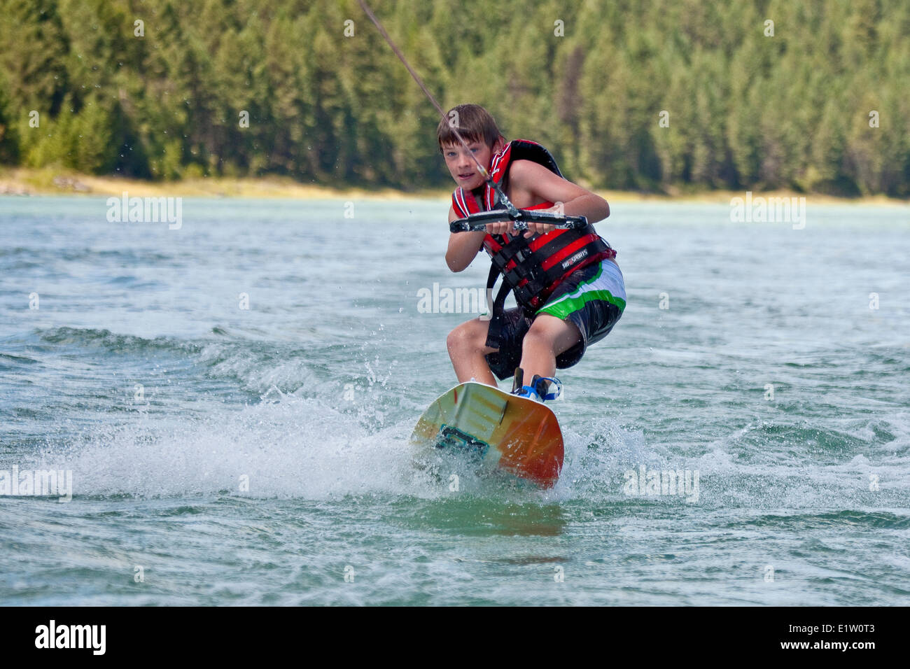 Young boy wakeboarding on Lake Koocanusa, East Kootenays, BC, Canada - Stock Image