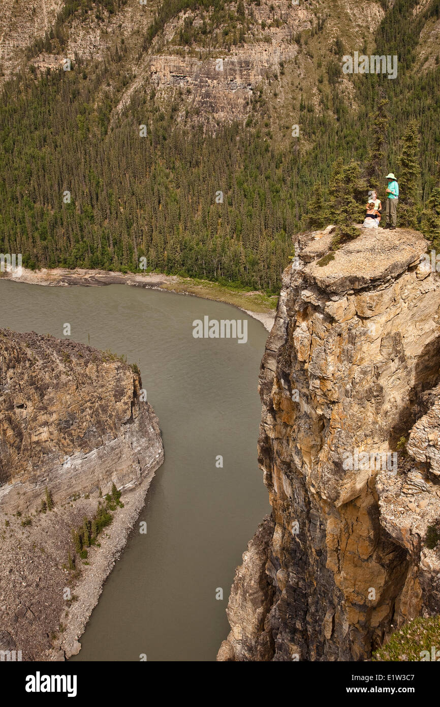 Three women view Nahanni River from cliff, Nahanni National Park Preserve, NWT, Canada. - Stock Image