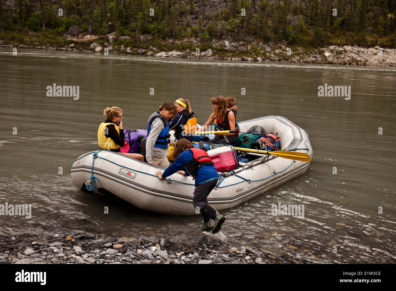 Young girl pushes raft from shore on Nahanni River, Nahanni National Park Preserve, NWT, Canada. Stock Photo