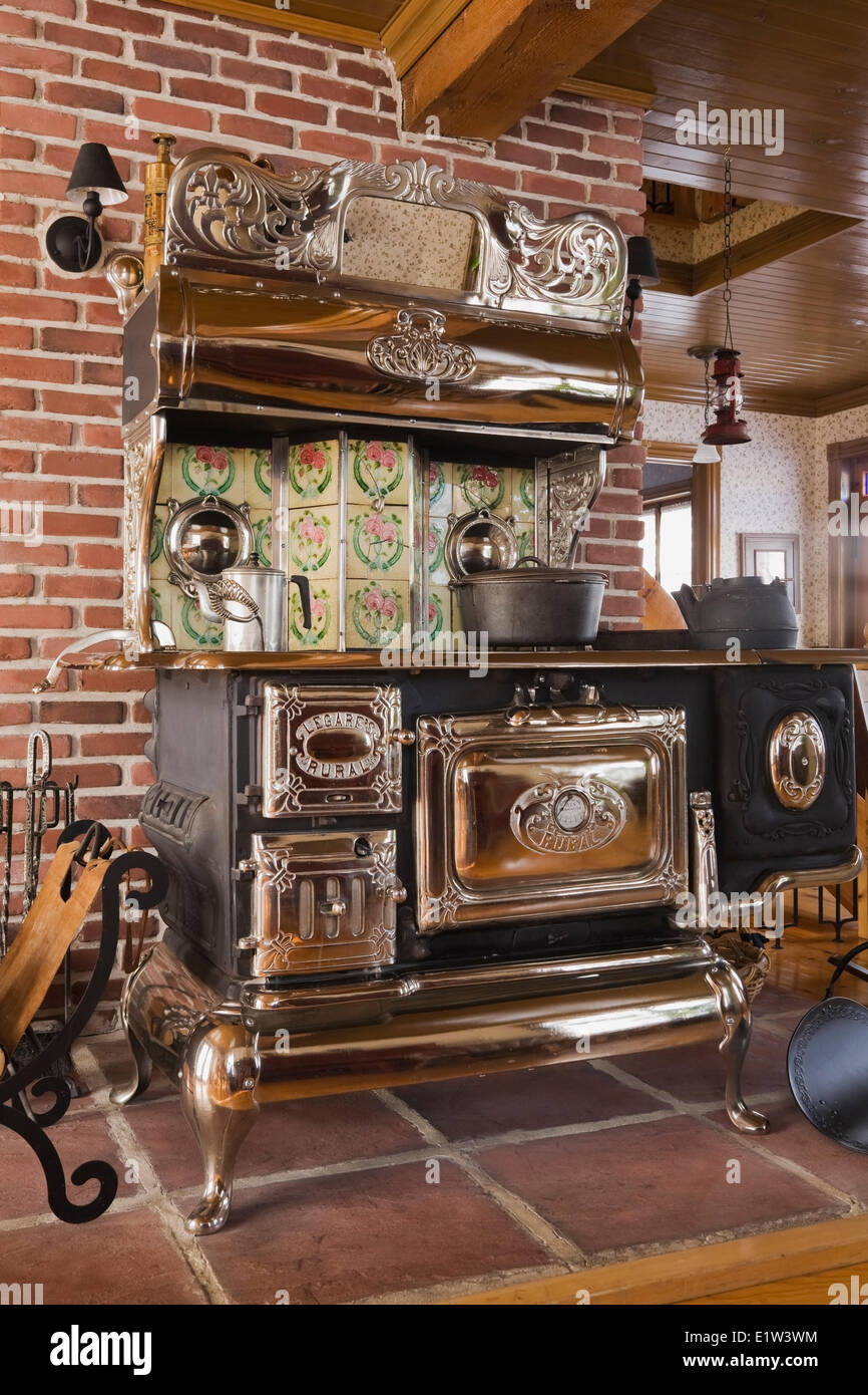 Old Legare's Rural antique wood stove in the living room a Canadiana cottage style fieldstone residential home built Stock Photo