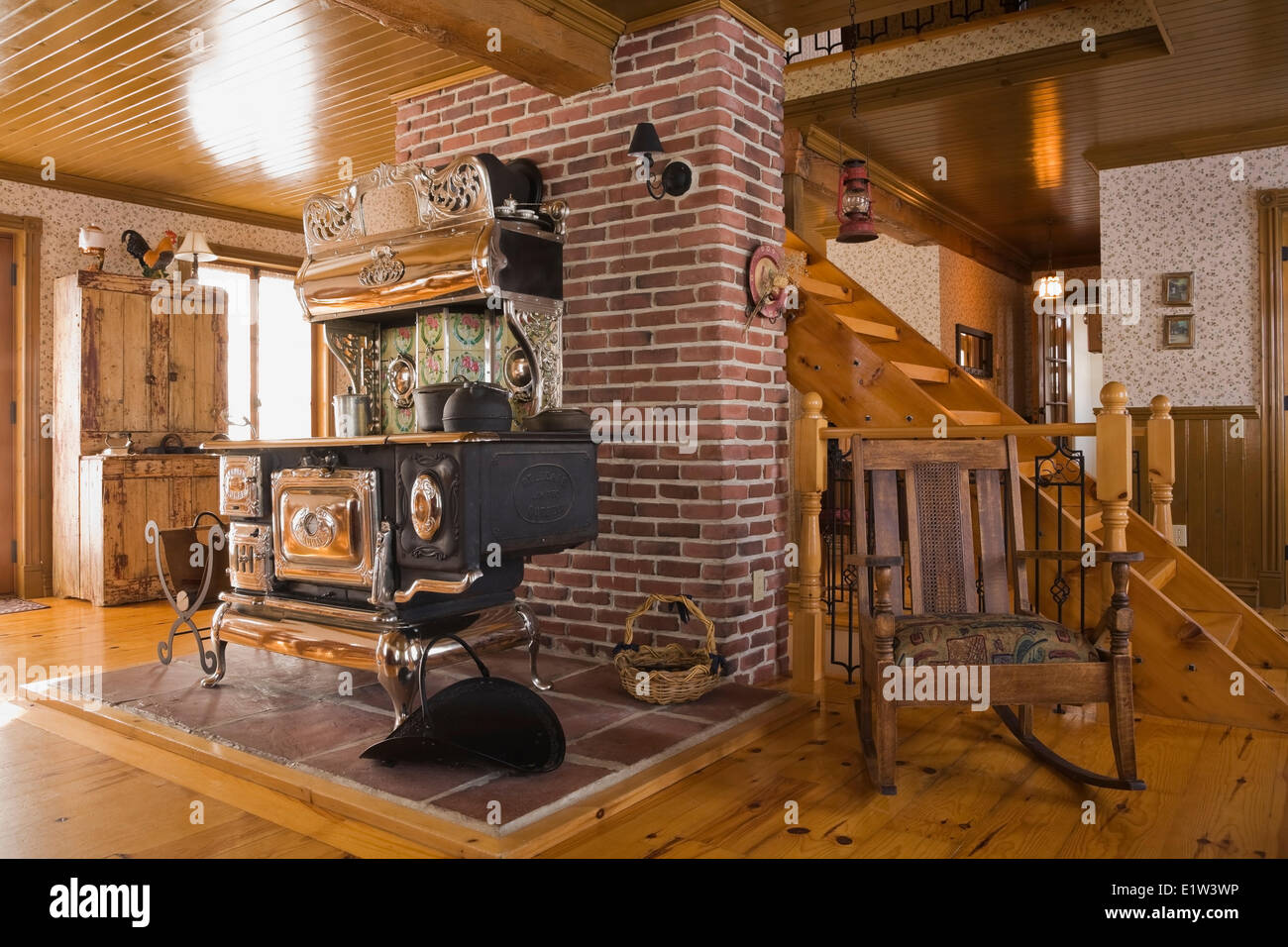 Old Legare's Rural antique wood stove in the living room a Canadiana cottage style fieldstone residential home - Stock Image