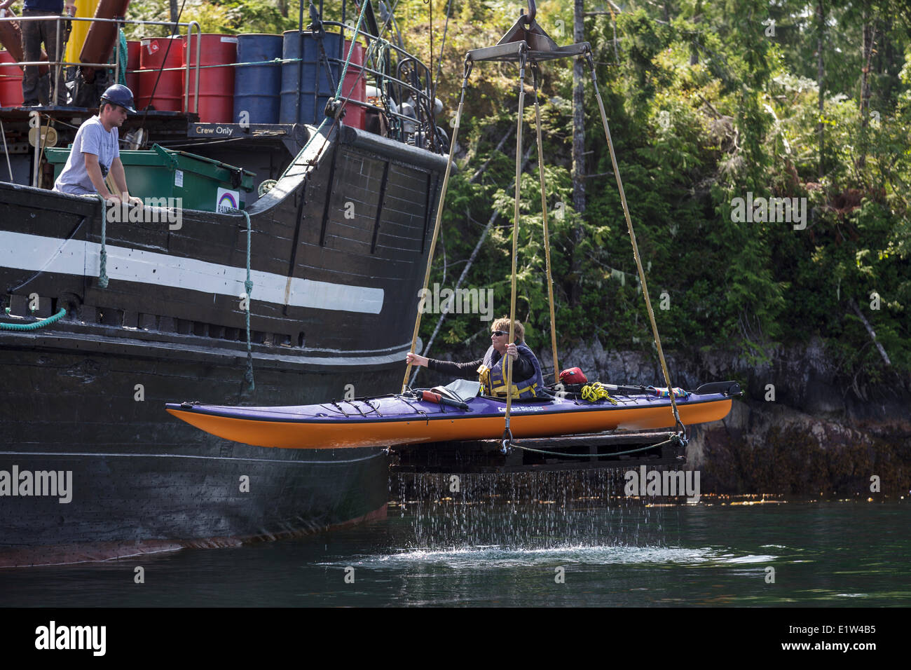 A kayaker is lifted onto the supply ship the Uchuck 111 at Flynn's Cove, Nootka Island, British Columbia, Canada. - Stock Image