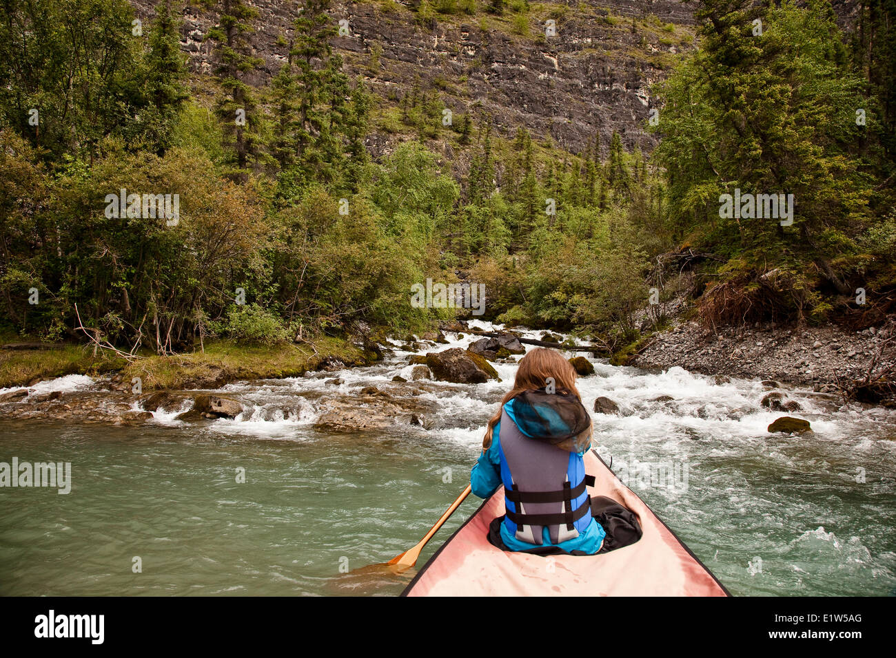 Young girl in canoe approaches White Spray Spring on Nahanni River, Nahanni National Park Preserve, NWT, Canada. - Stock Image