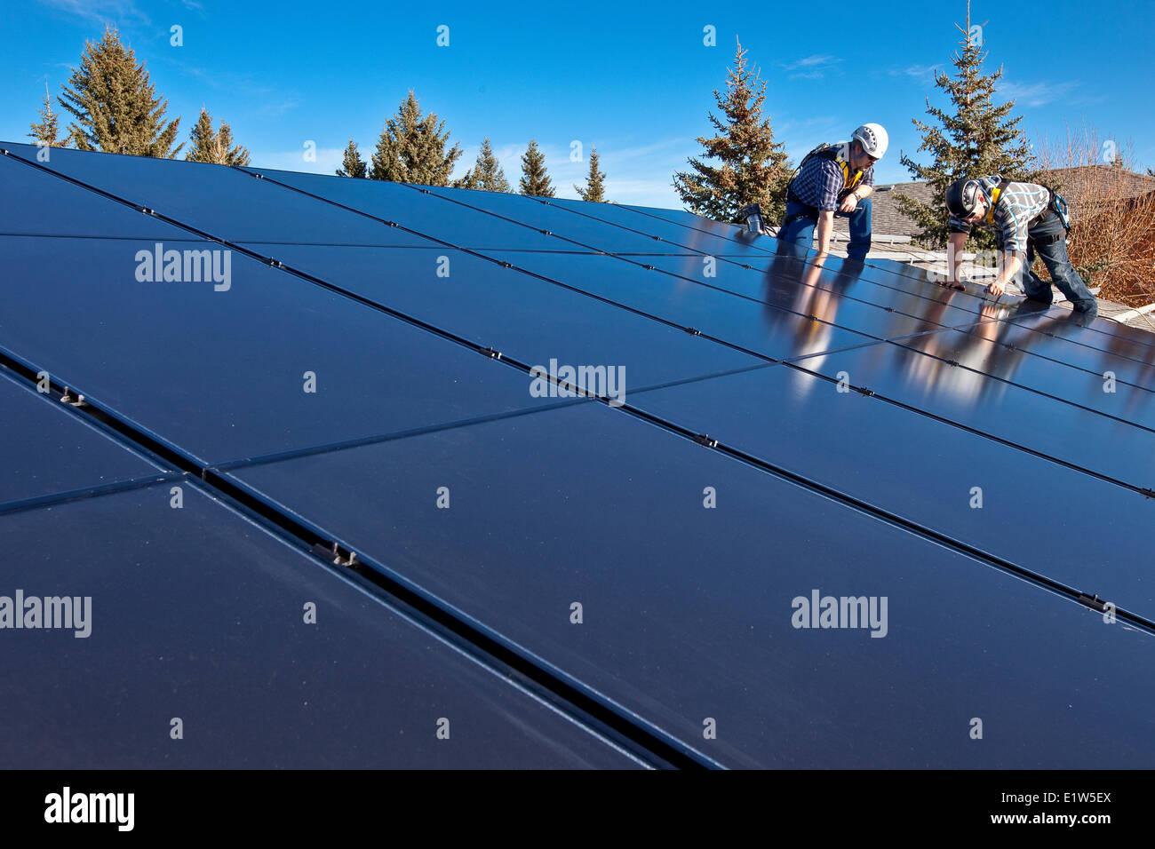 Two solar panel installers install solar panels on roof, Alberta foothills near Black Diamond, Alberta, Canada. - Stock Image