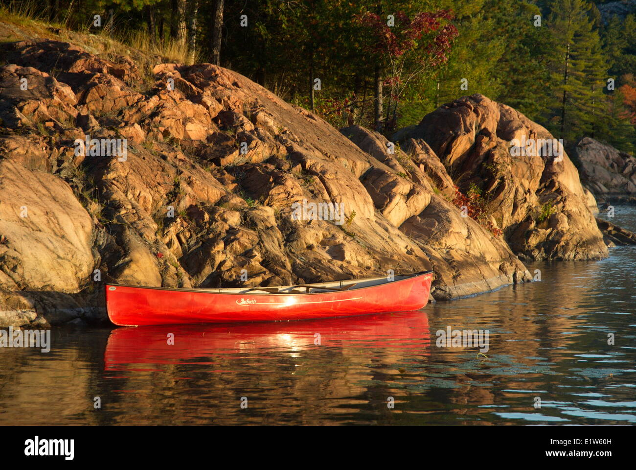 Red Canoe along a rocky shore on George Lake, Kilarney provincial park, Ontario Stock Photo