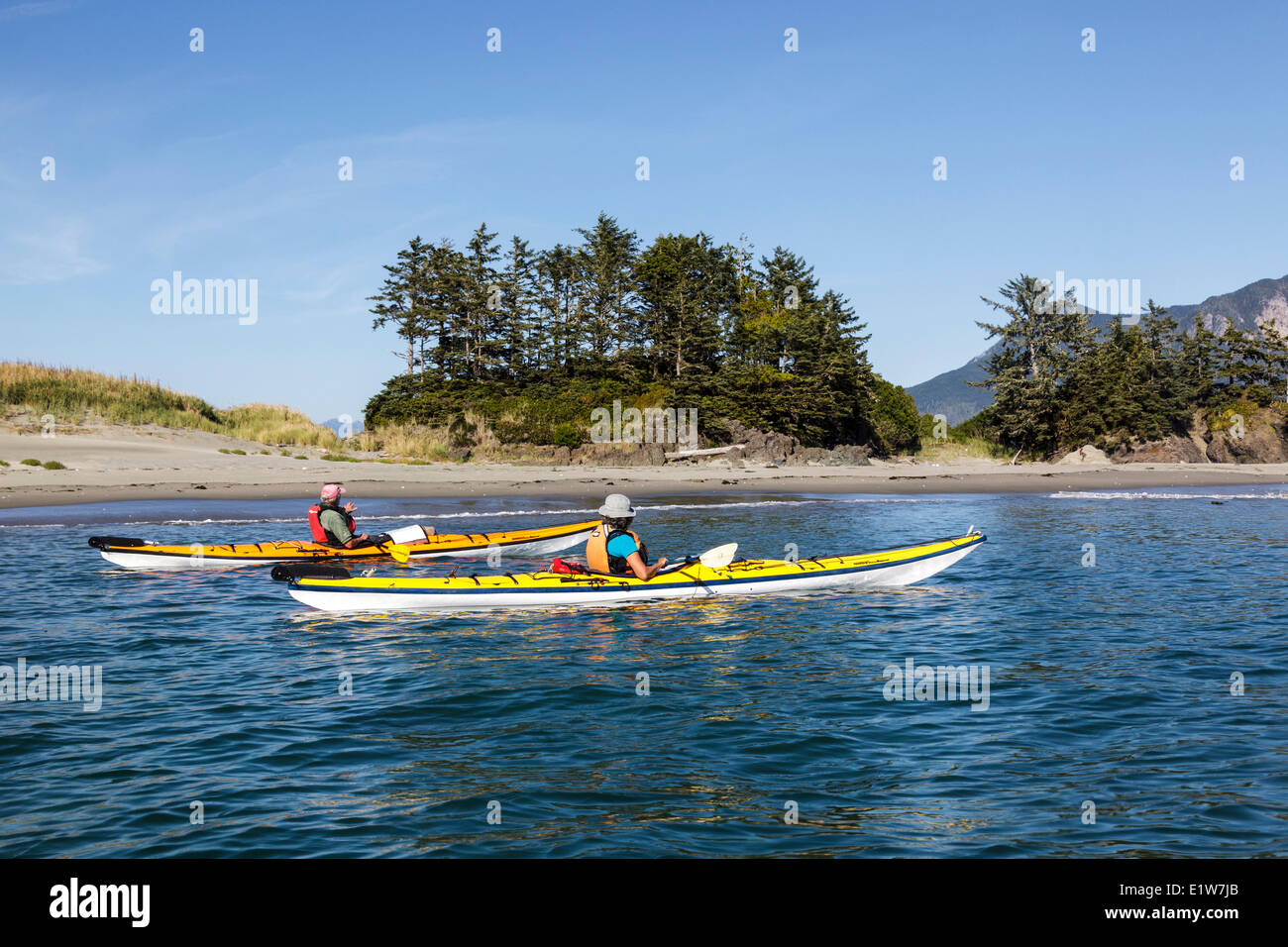 Two kayakers approach Whalers Islet in Clayoquot Sound off the west coast of Vancouver Island, British Columbia, - Stock Image