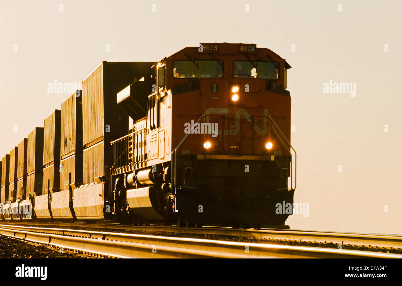 A locomotive pulls rail cars carrying containers near Winnipeg, Manitoba, Canada - Stock Image