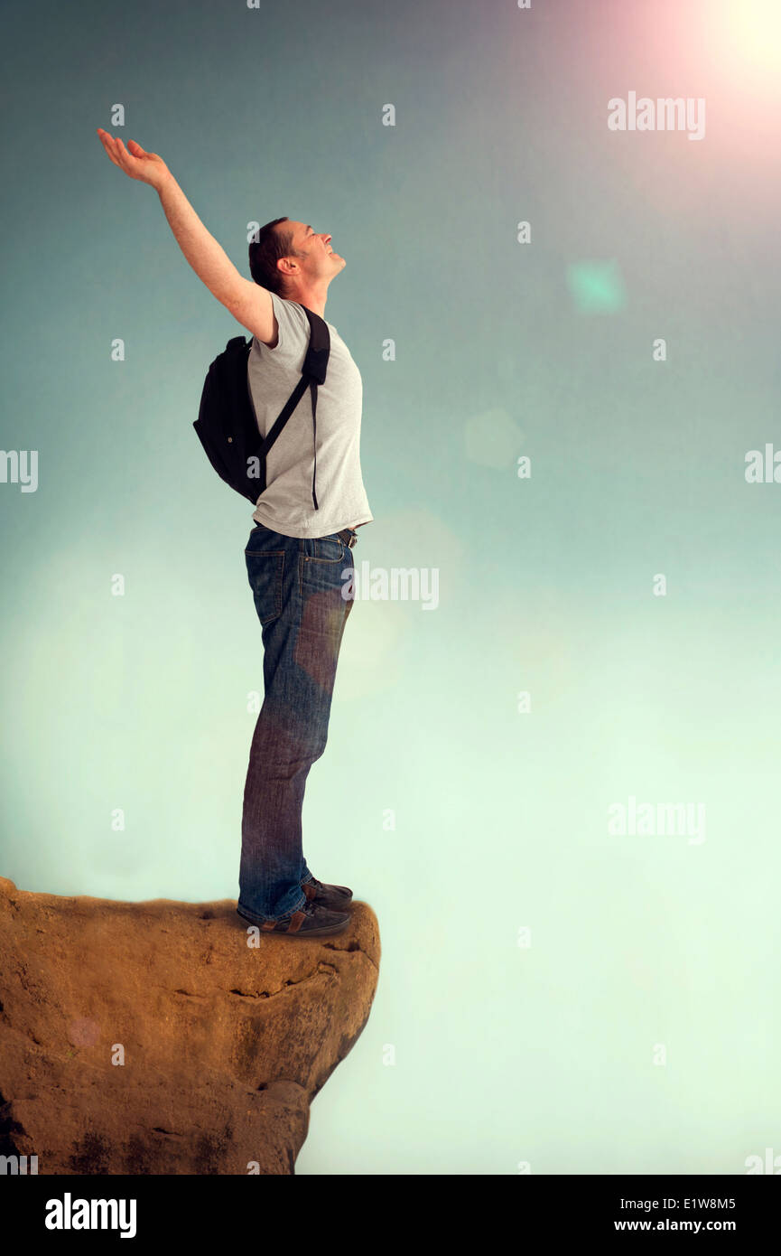 joyous man arms aloft giving praise on a rocky outcrop outside backpacking - Stock Image