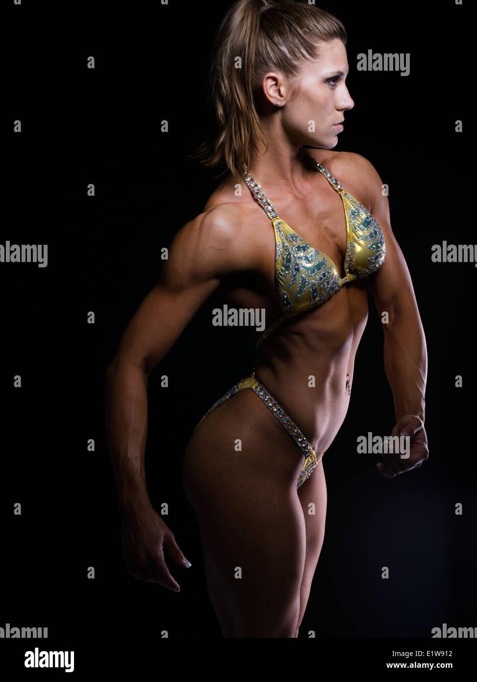 Muscular toned athletic woman - female body builder bodybuilder fitness model - Stock Image