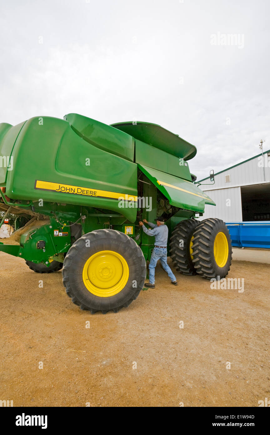 Farmer adjusts belts on a combine parked in his farmyard, near Ponteix, Saskatchewan, Canada - Stock Image