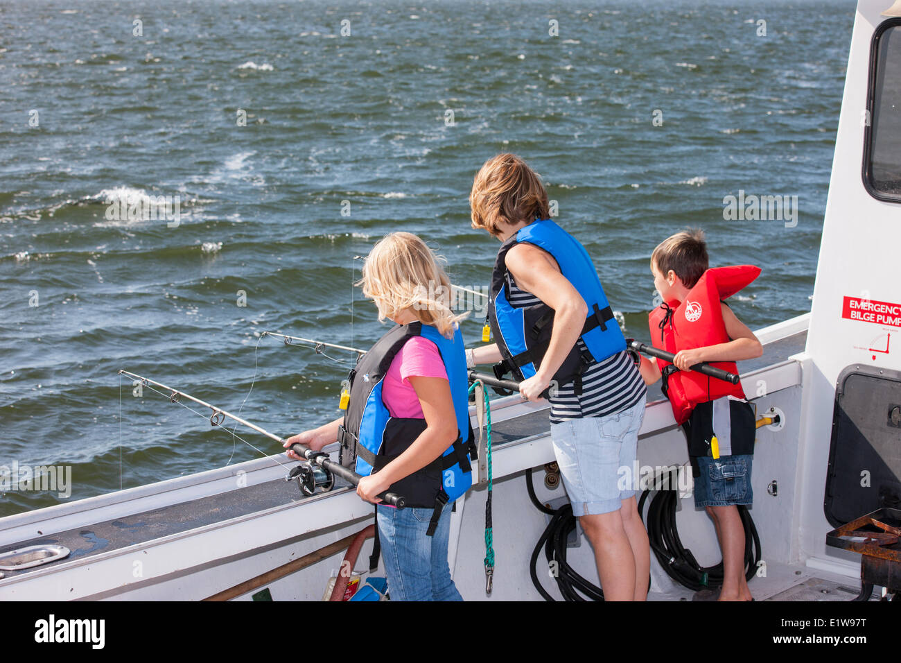 mother, son and daughter deep-sea fishing, Northport, Prince Edward Island, Canada - Stock Image