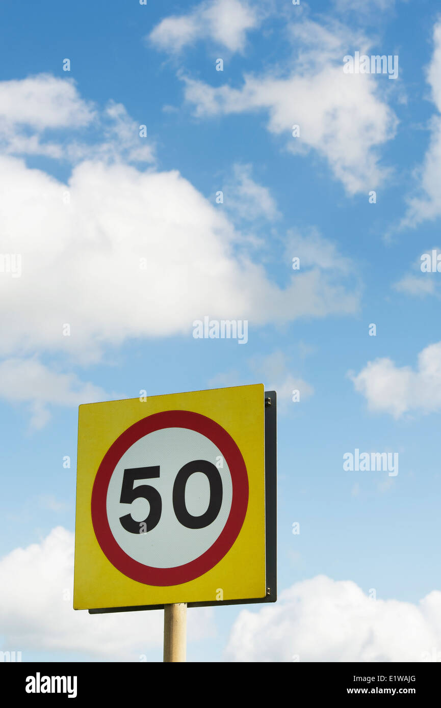 50 MPH Speed limit road sign against blue cloudy sky. England - Stock Image