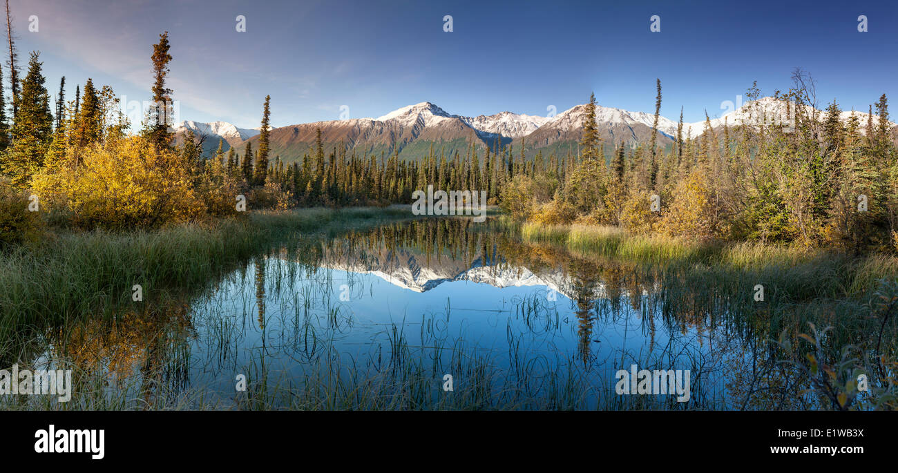 Reflected snow dusted mountains in the Kluane Range the St. Elias Mountains south Beaver Creek Yukon along the Alaska - Stock Image
