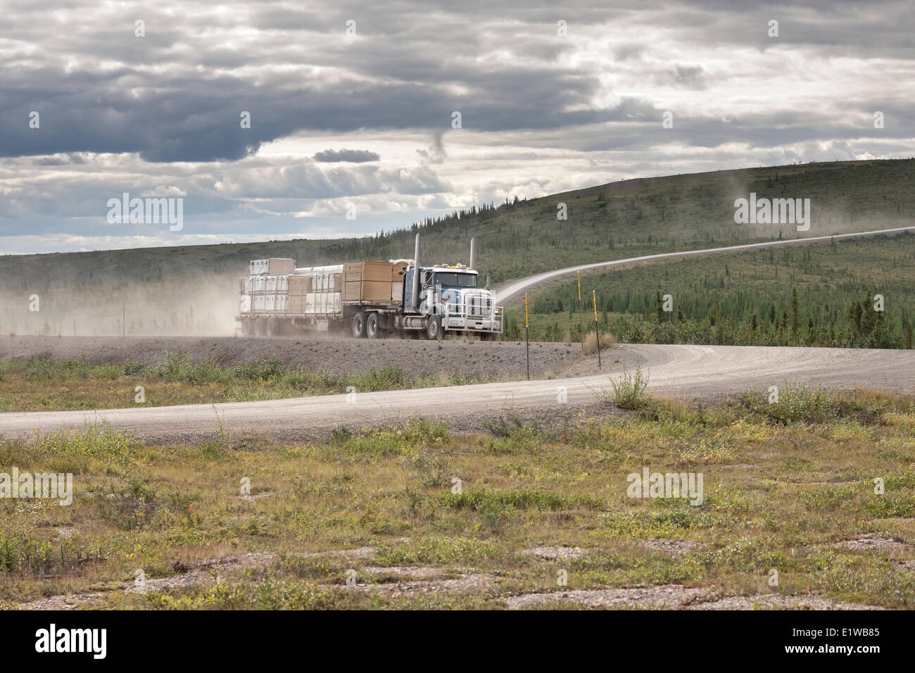 A transport truck driving on the dusty Dempster Highway in the Yukon Territory, Canada - Stock Image