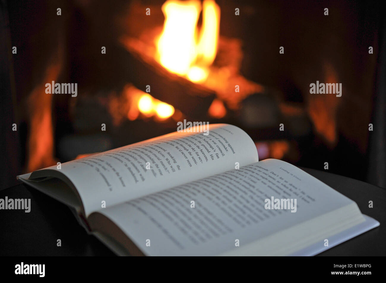 Open book by a fireplace - Stock Image