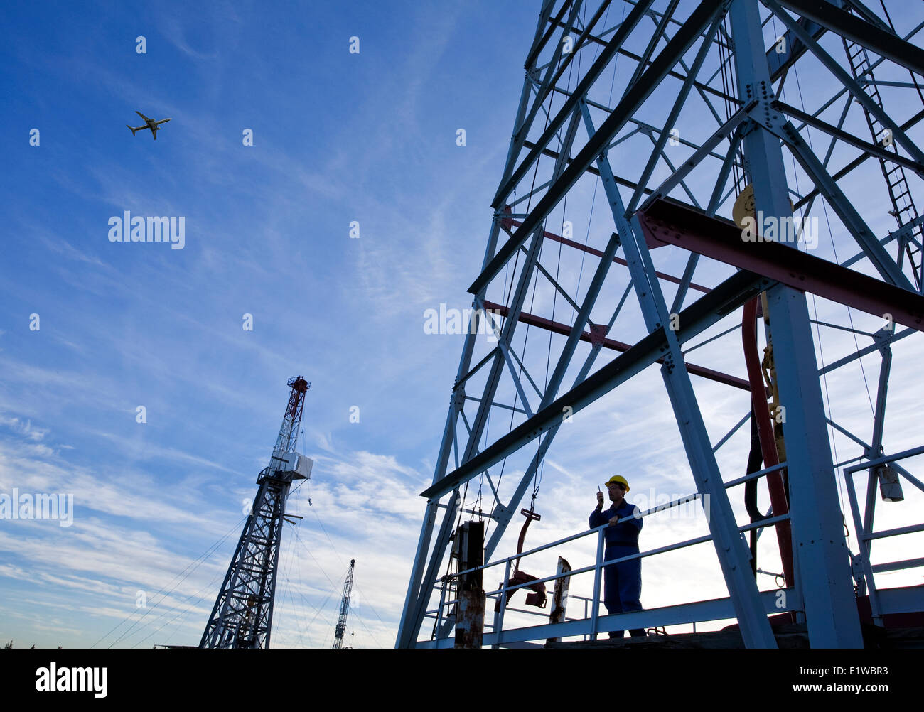 Drilling rig worker talking on radio on platform with airplane flying overhead, Alberta, Canada Stock Photo