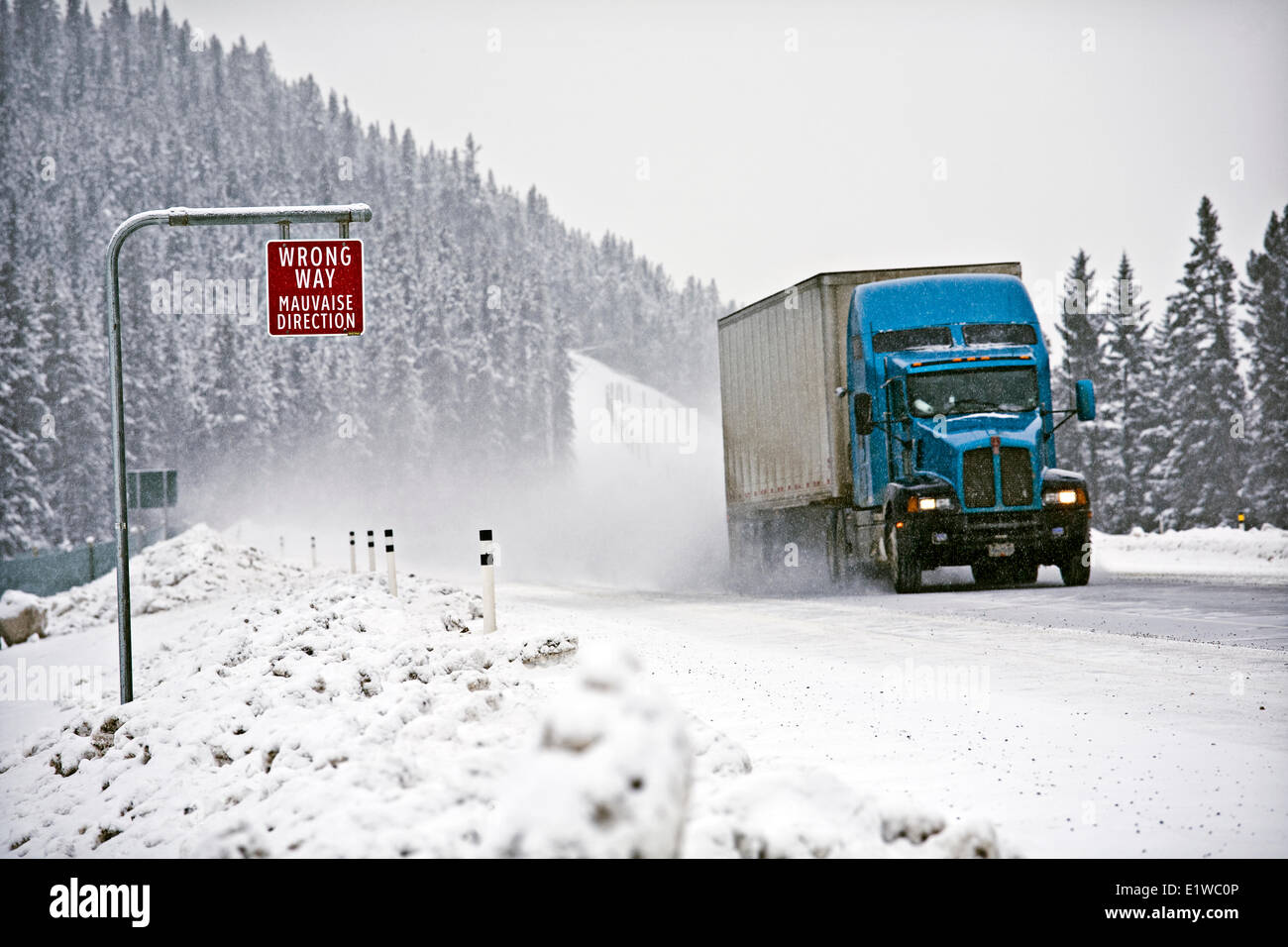 Wrong way sign and transport truck on Trans-Canada Highway in winter conditions near Lake Louise, Alberta, Canada. - Stock Image
