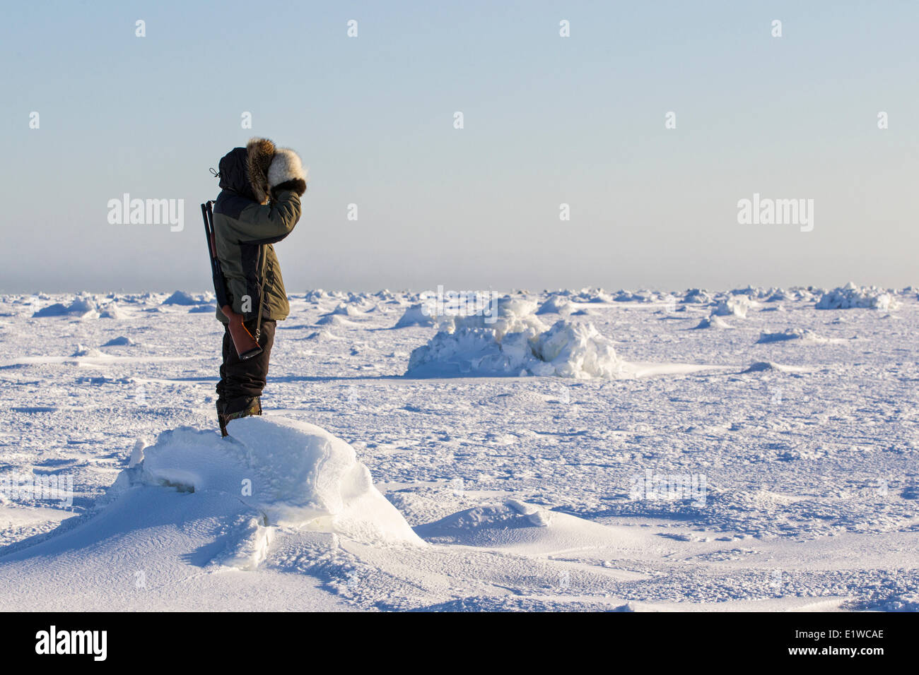 Inuit man scanning ice for polar bears, west coast Hudson Bay, south of Arviat, Nunavut, Canada - Stock Image
