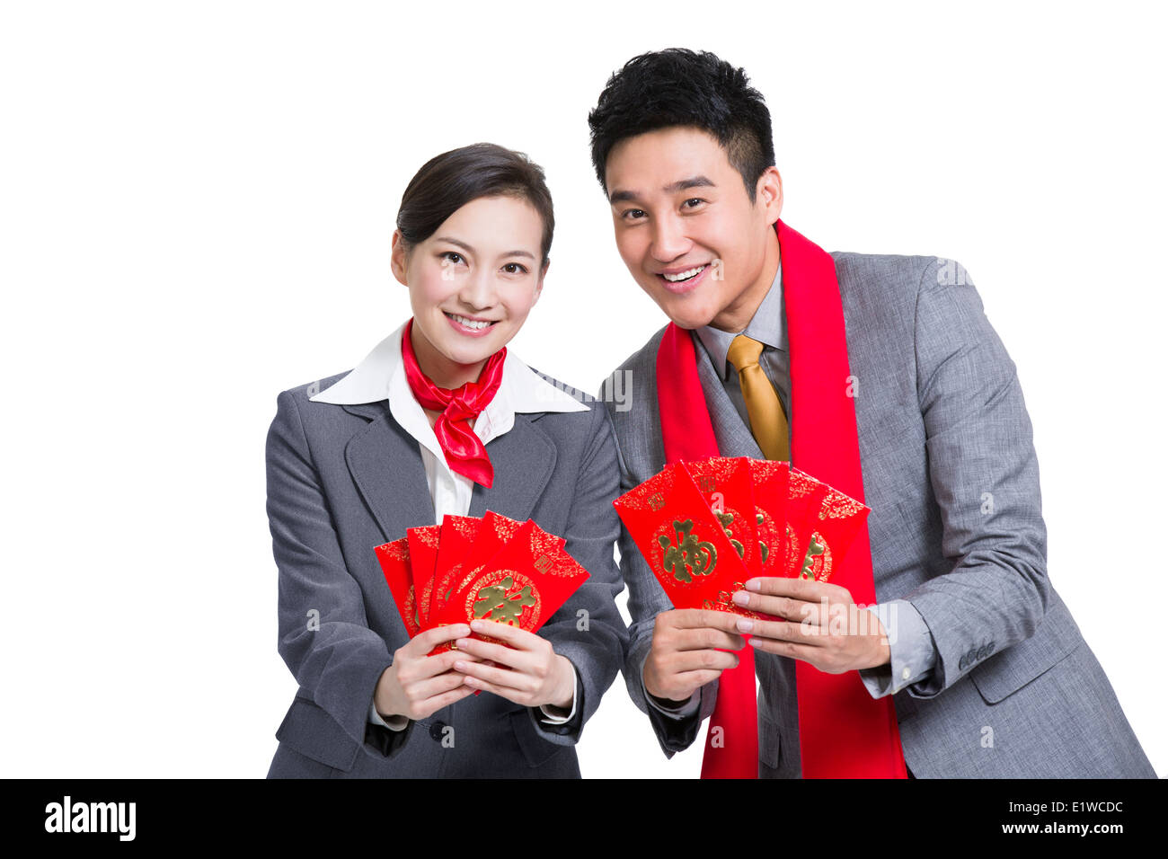 Happy business colleagues gifting traditional red envelopes - Stock Image