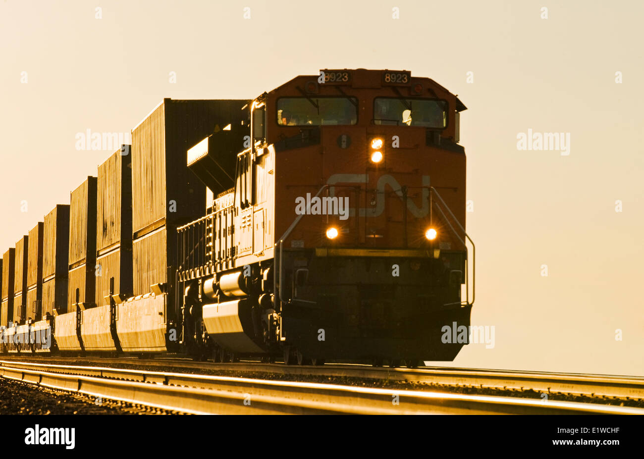 locomotive pulling rail cars carrying containers, near Winnipeg, Manitoba, Canada - Stock Image
