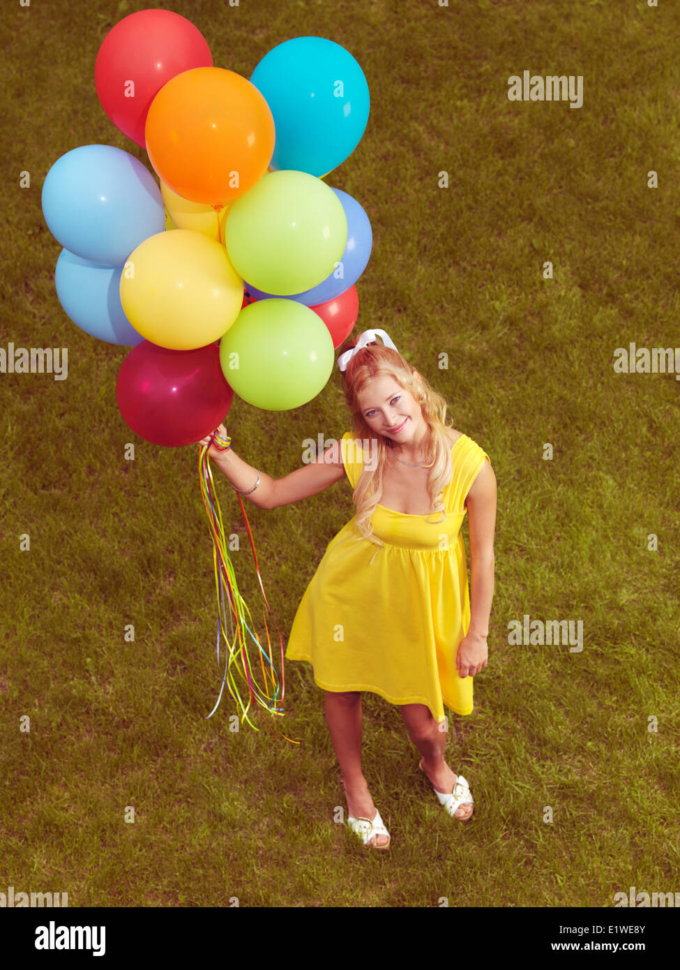 Young smiling woman standing on grass with a bunch of colorful helium balloons in her hand. Retro stylized image. - Stock Image